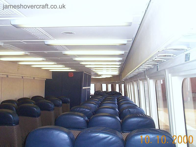 SRN4 systems tour - Looking forward in the starboard passenger cabin. The SRN4 Super-4 was capable of holding 424 passengers and 60 cars in the configuration used by Seaspeed/Hoverspeed. Here is shown the final layout of the cabin before the craft's retirement in 2000. Note the forward galley (blue box like structure), in the approximate position of the front pylon and lift fan assembly, and the pull-down life-jackets for passengers in the overhead compartments. (James Rowson).
